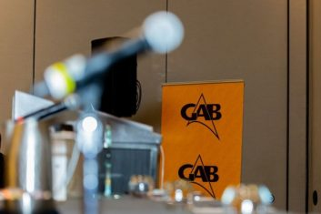 Photo of the GAB logo on a banner behind a microphone