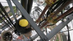 Photo of crew installing coaxial cable hangers on a tower